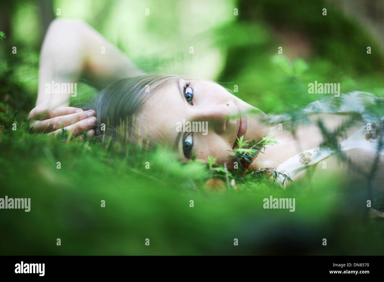 Girl lying on the forest floor, portrait - Stock Image