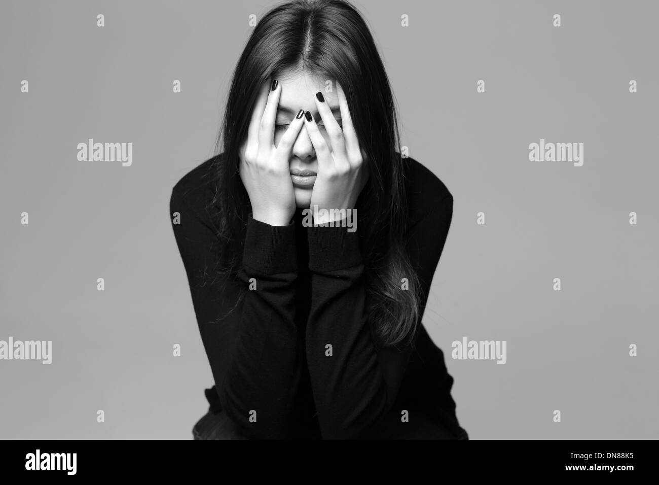 Black and white photo of a depressed young woman with hands over her head - Stock Image