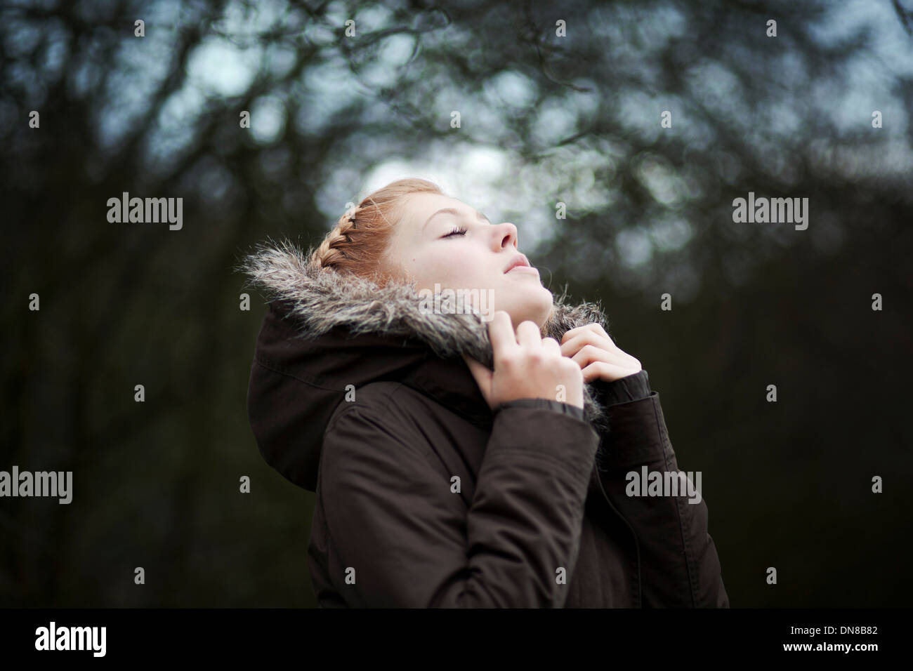 Woman with eyes closed snuggles in winter jacket - Stock Image