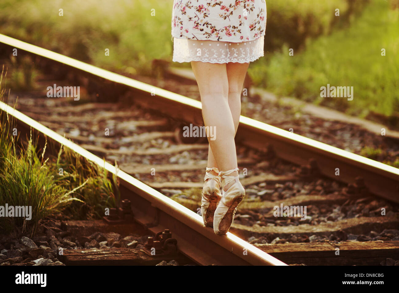 Young woman in dress balancing on a railway track - Stock Image