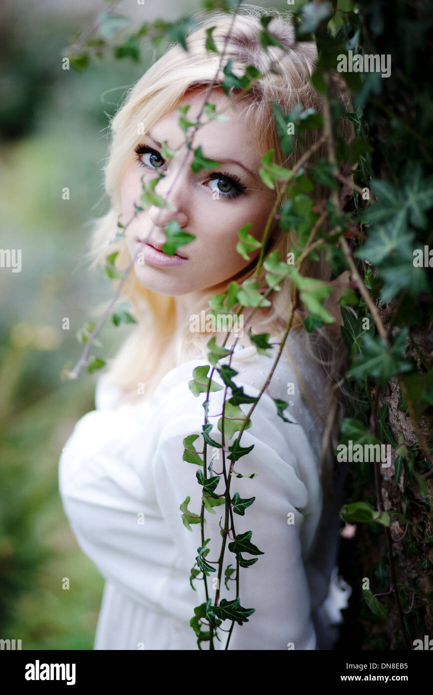 Young woman leaning against a ivy hedge, portrait - Stock Image