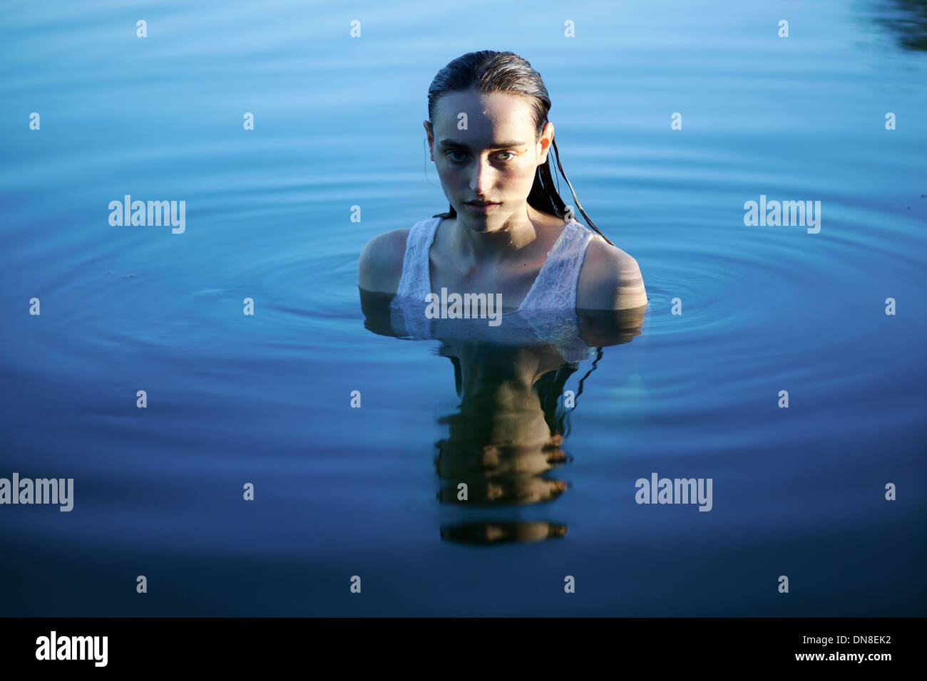 Young woman standing in water, portrait - Stock Image