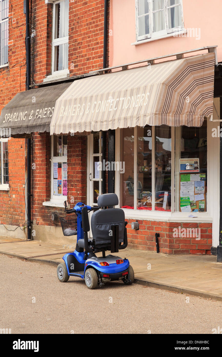 Mobility scooter parked in street outside a village local Baker's shop in Lavenham, Suffolk, East Anglia, England, UK, Britain. - Stock Image