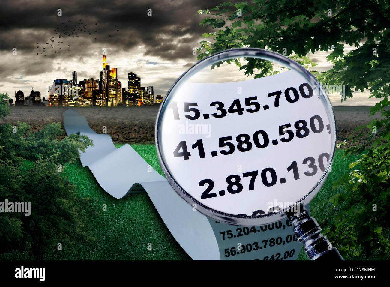 Magnifier shows the enlargement of high sums. In the background a large city can be seen. - Stock Image