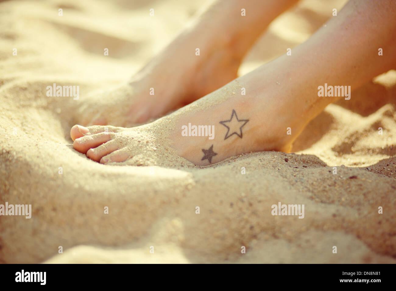 Feet with tatoo on the sandy beach - Stock Image