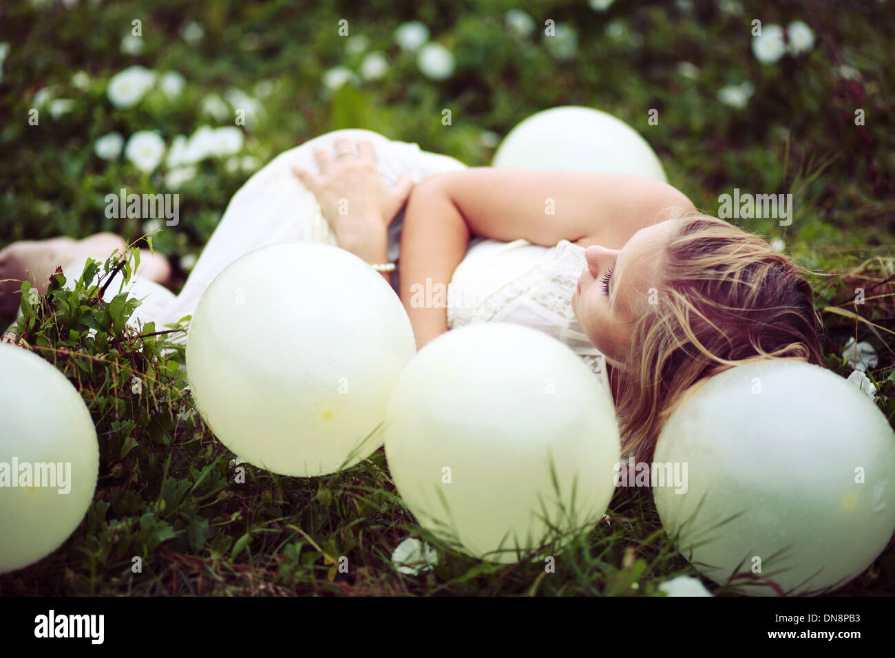 Young woman lying on a meadow between balloons - Stock Image