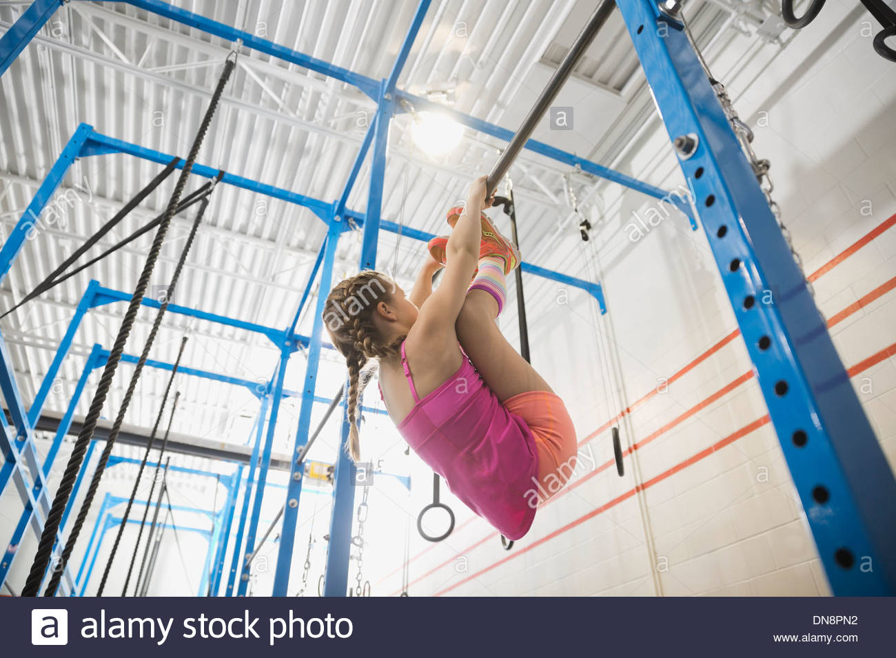Girl practicing toes-to-bar move - Stock Image