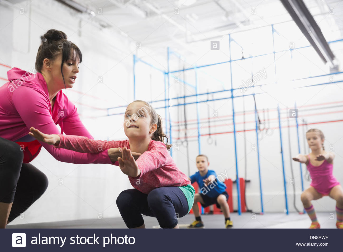Coach assisting girl with squats in Crossfit class - Stock Image
