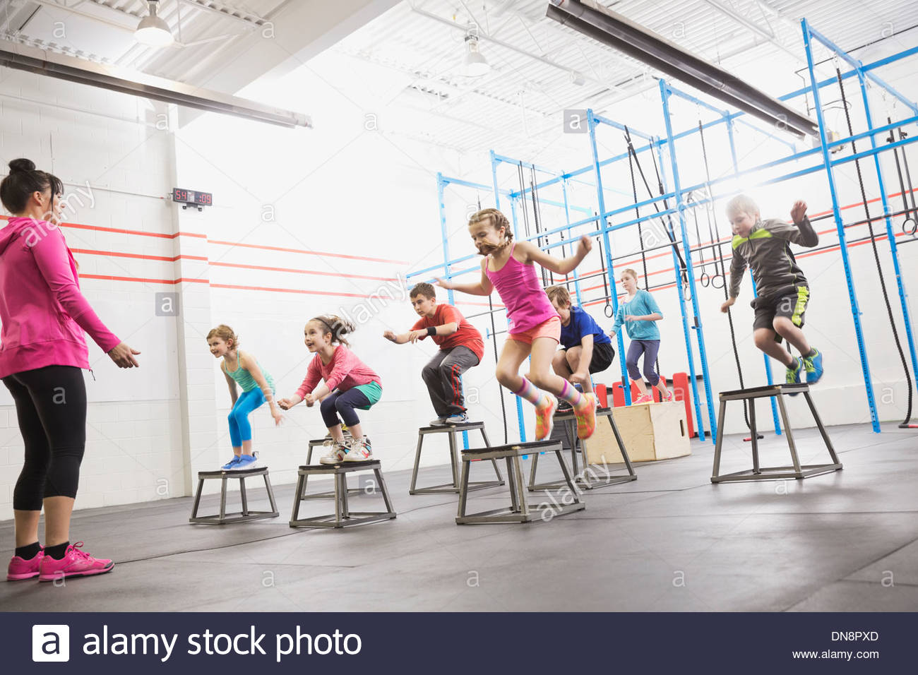 Children doing box jumps at gym - Stock Image