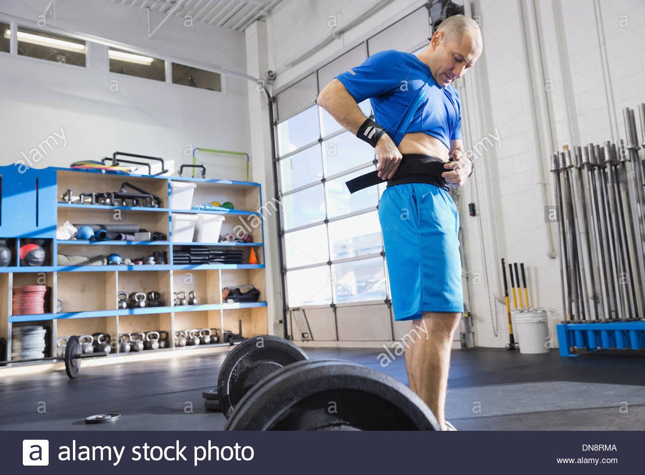 Man adjusting weight lifting belt - Stock Image
