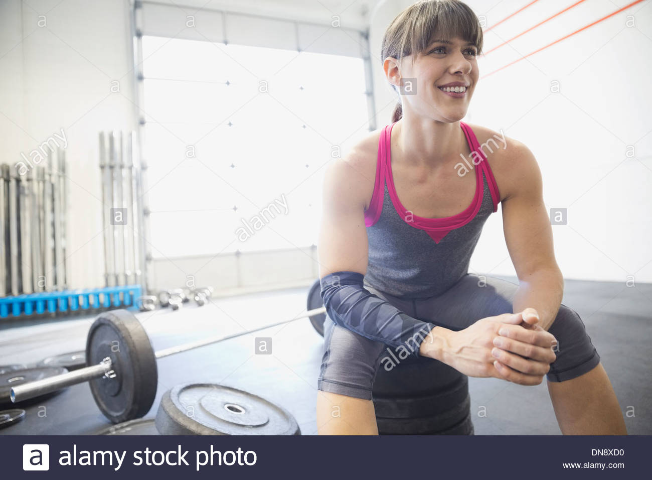 Woman sitting on weights in gym - Stock Image