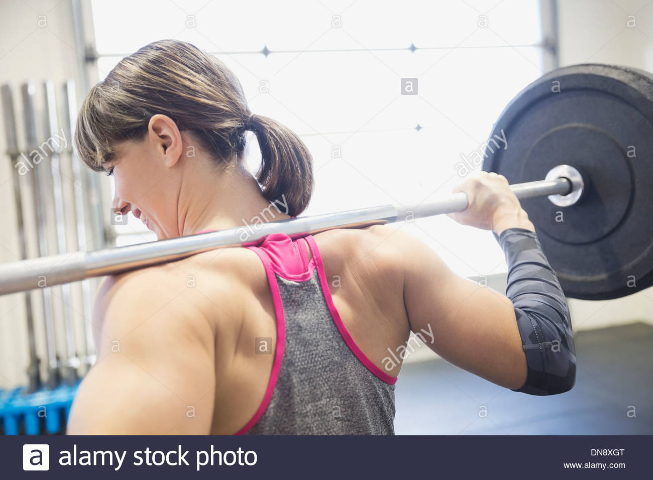 Woman standing with barbell on shoulders - Stock Image
