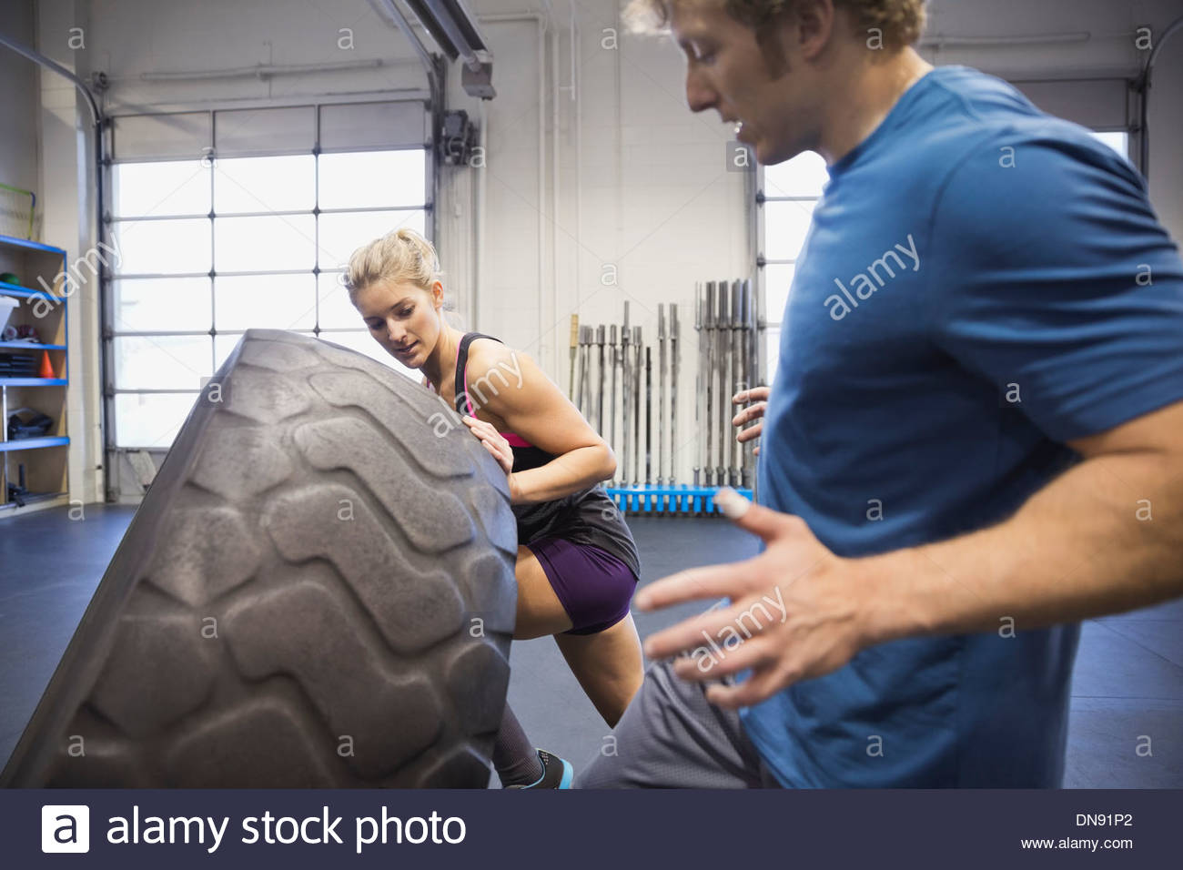 Instructor guiding woman in tire-flip workout - Stock Image