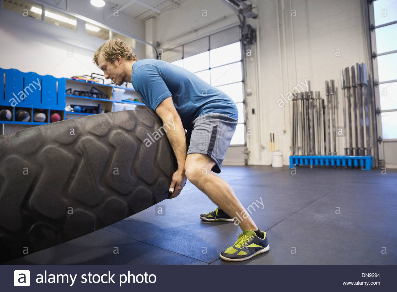 Man doing tire-flip exercise in Crossfit gym - Stock Image