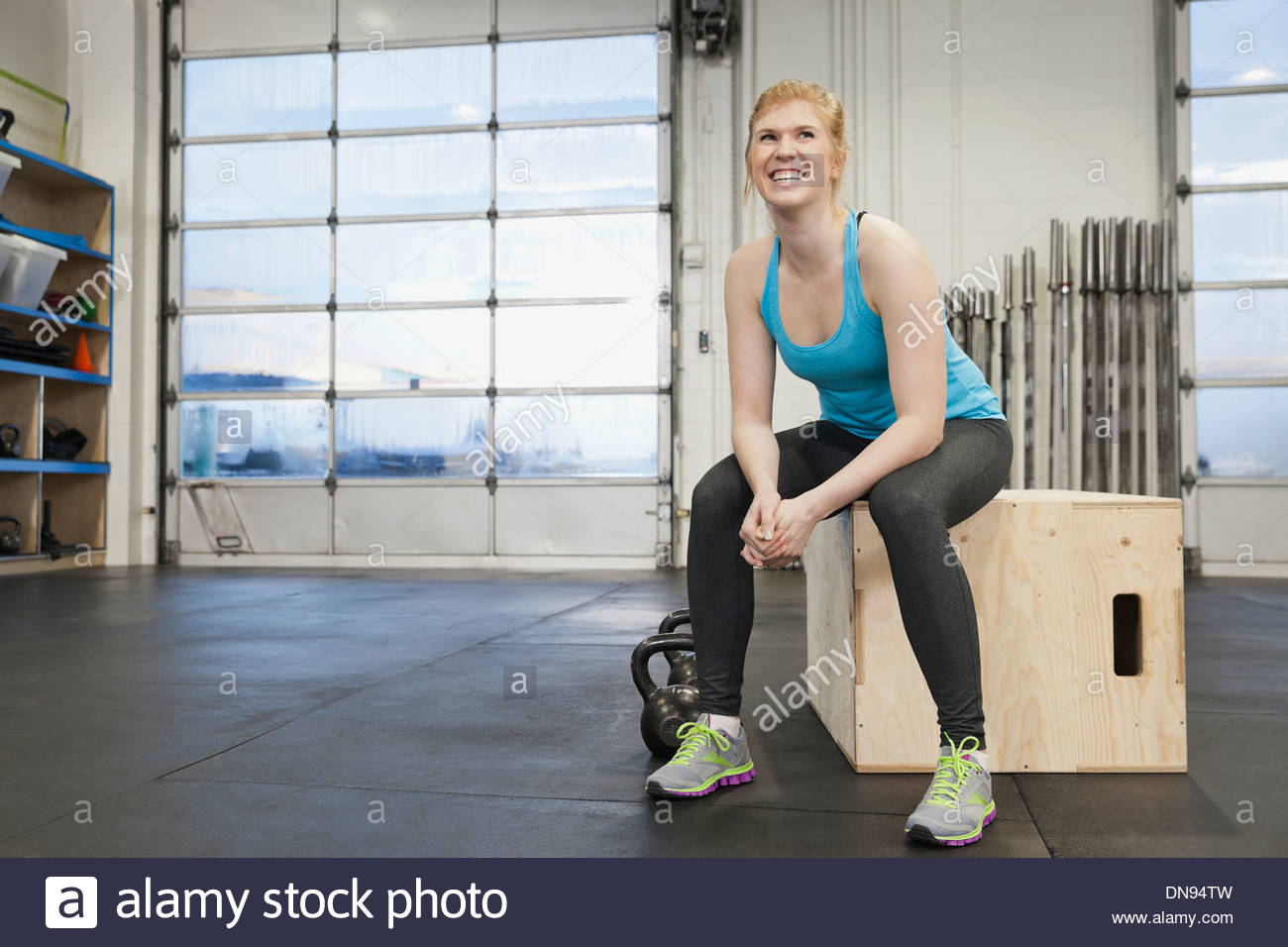 Woman sitting on box in gym - Stock Image