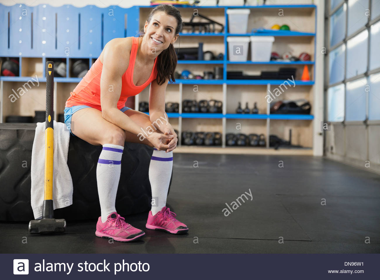 Woman sitting on tire in Crossfit gym - Stock Image