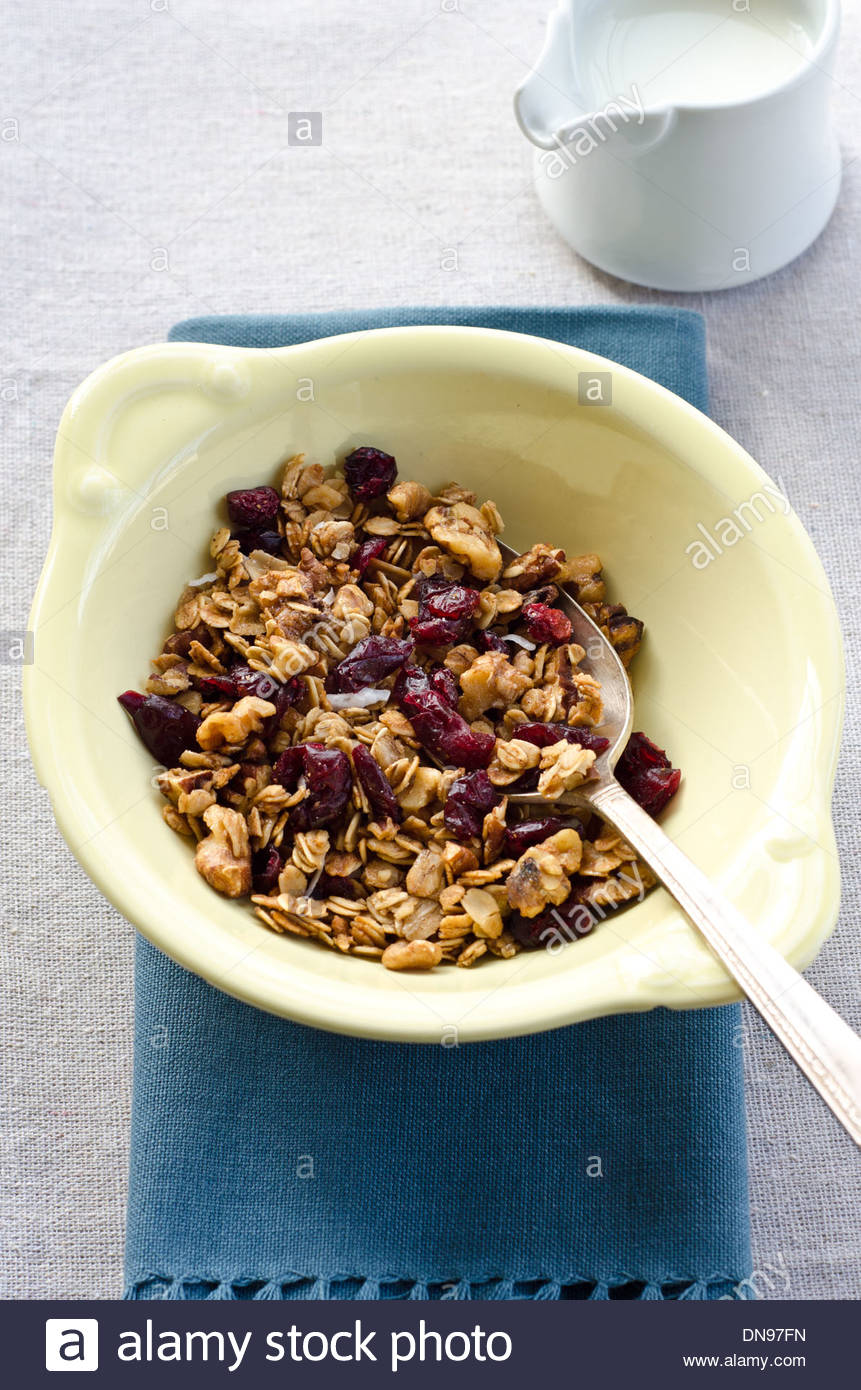 Homemade granola in bowl with spoon and blue napkin next to small pitcher of milk. - Stock Image