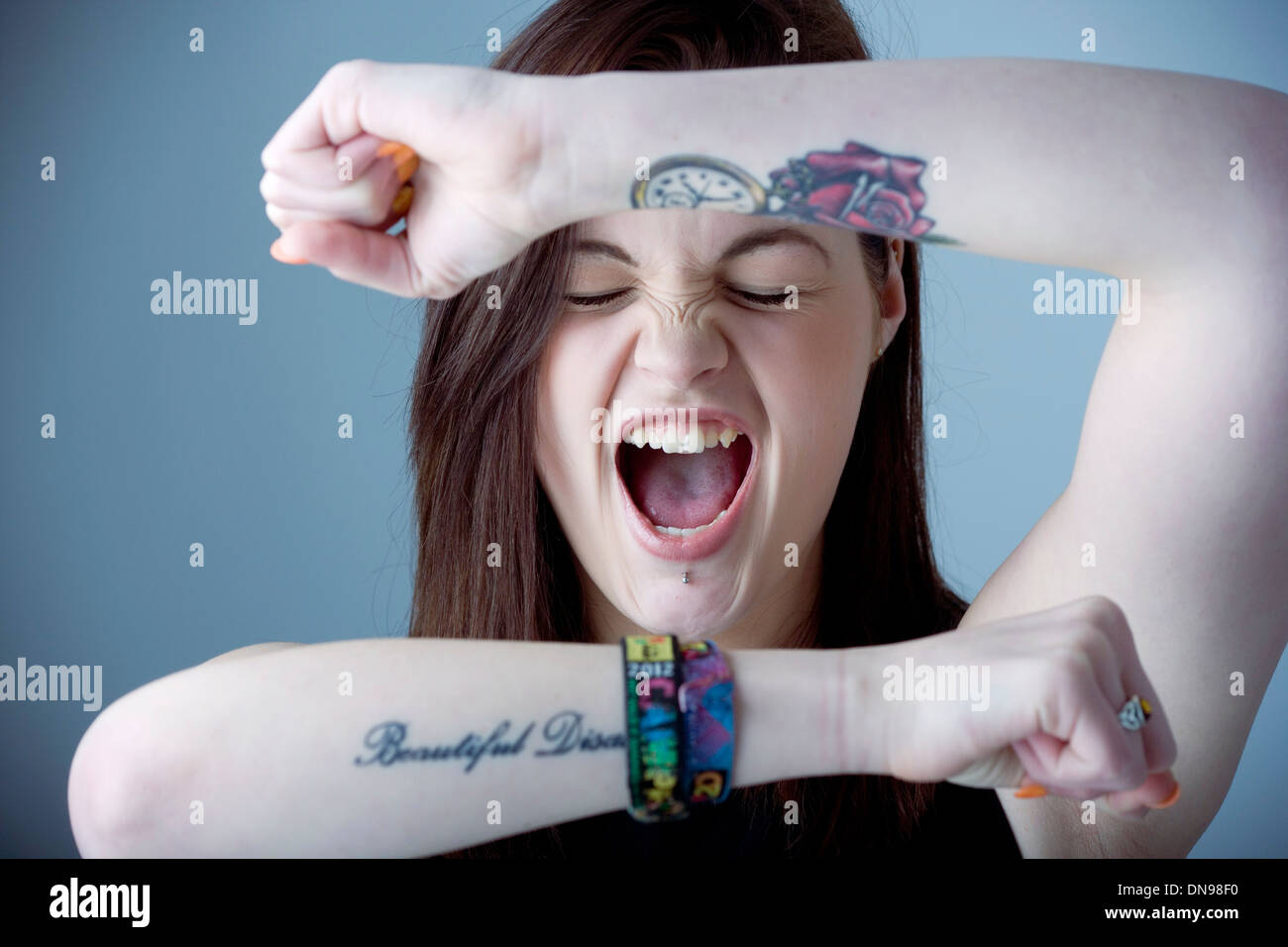 Teenage girl screaming with raised arms. - Stock Image
