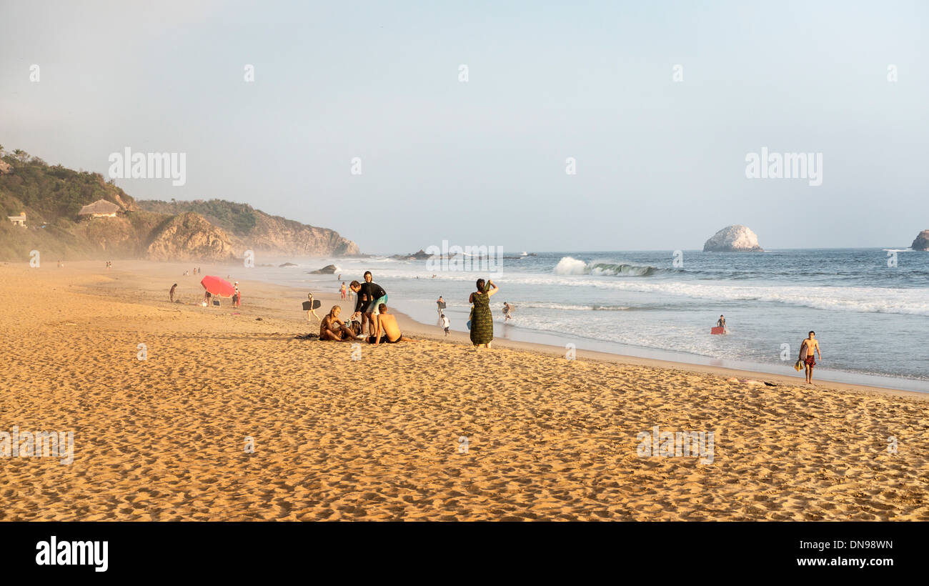groups of people socializing on beach or enjoying  swimming in sea as sun is setting over San Agustinillo Oaxaca State Mexico - Stock Image