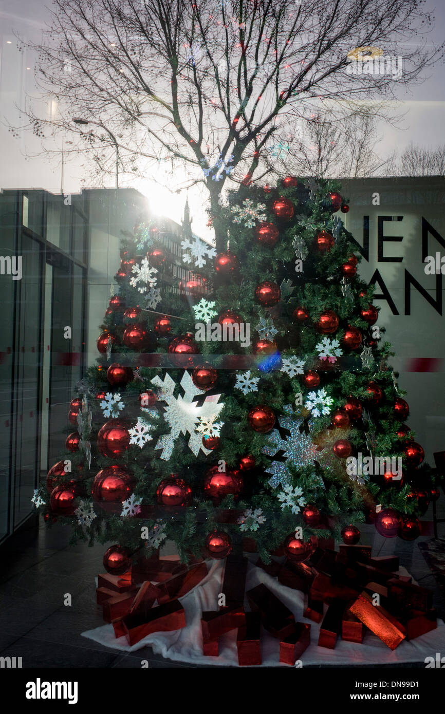 Merging of artificial Christmas tree and real, natural tree in the background, seen through a corporate foyer window. - Stock Image