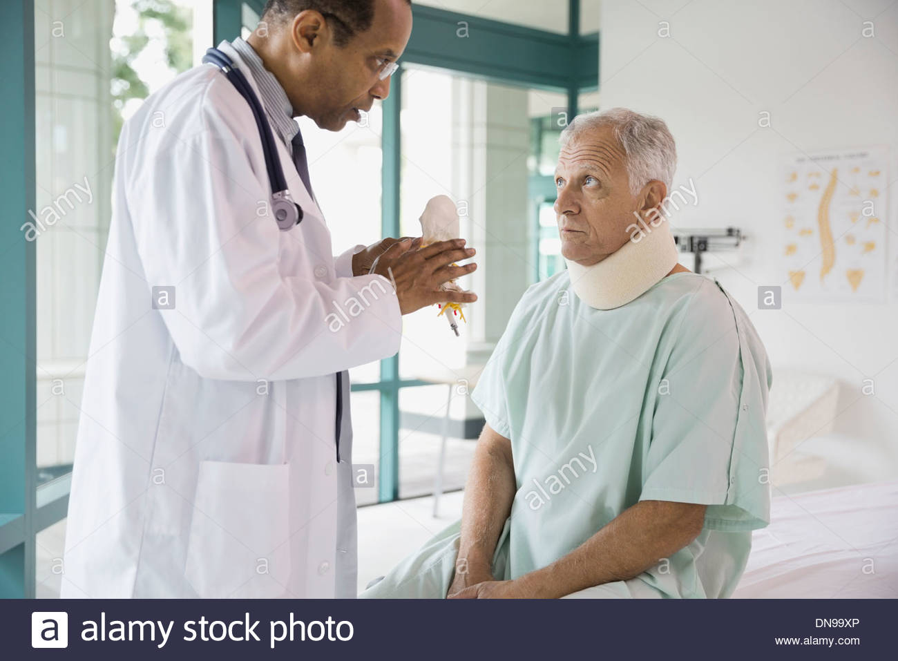 Doctor explaining model to patient suffering from neck pain - Stock Image