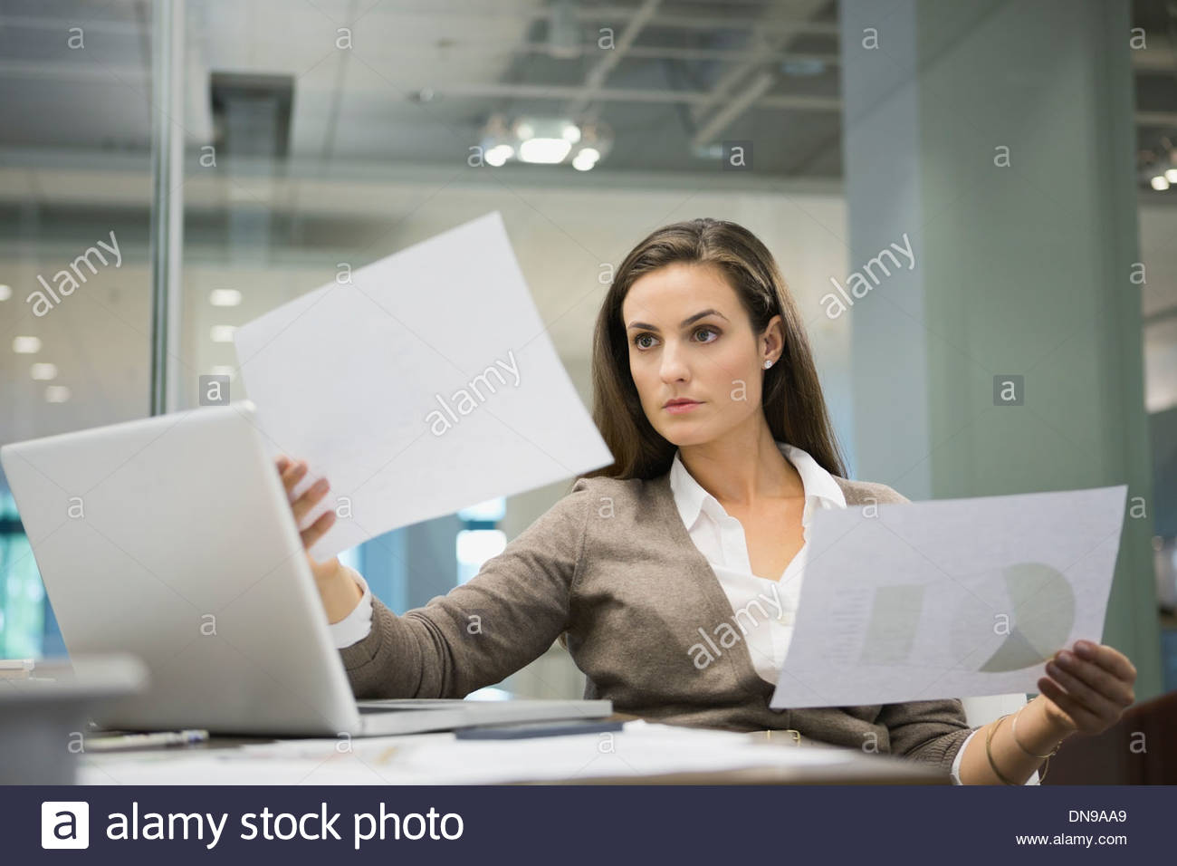 Businesswoman analyzing documents in office - Stock Image