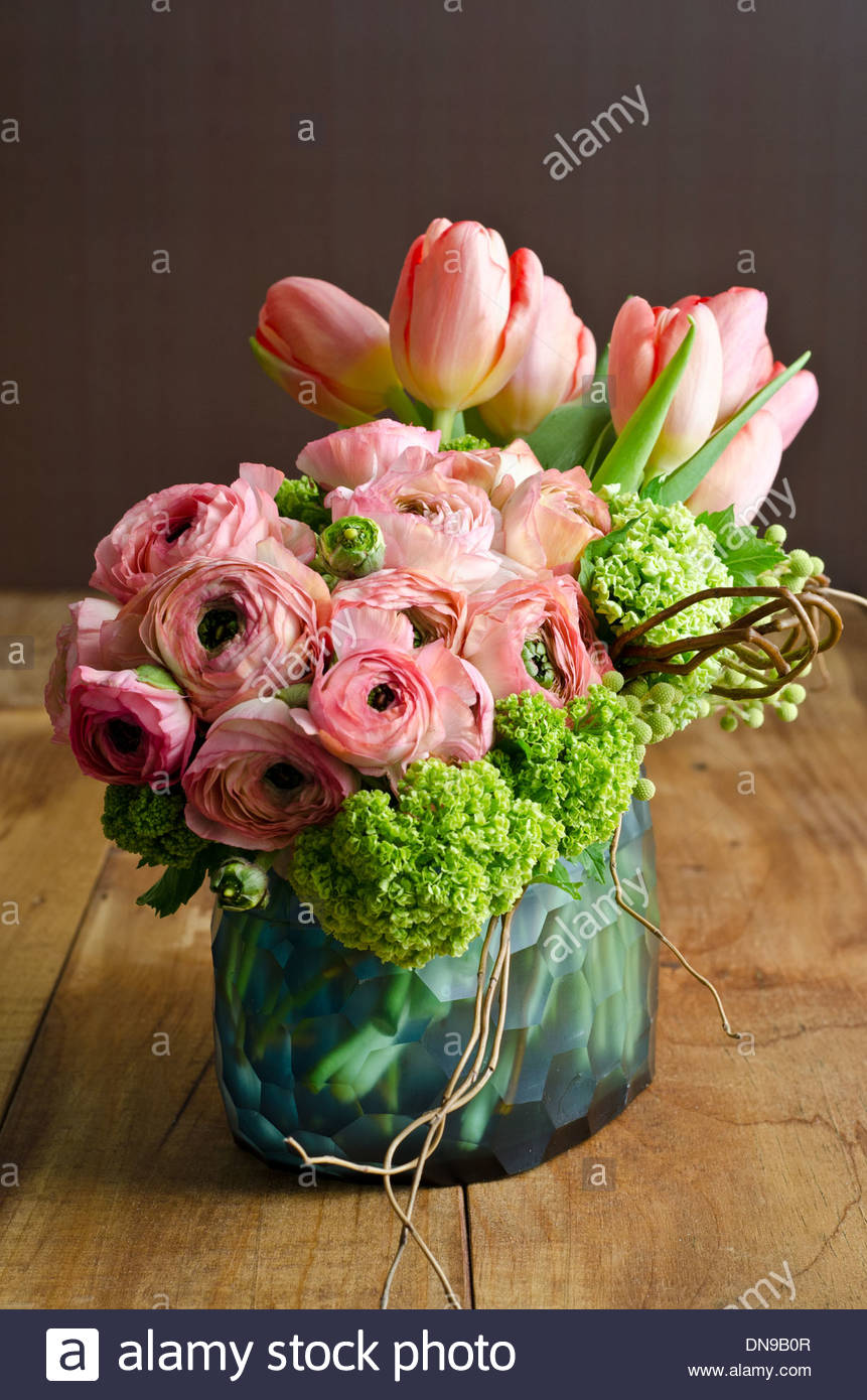 Spring flower arrangement with pink tulips and ranunculus in blue spring flower arrangement with pink tulips and ranunculus in blue glass vase on wooden table mightylinksfo