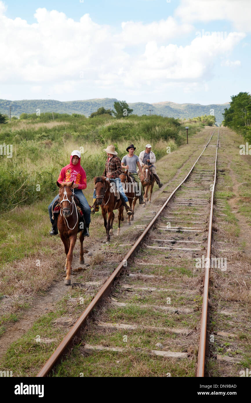 People riding horses by the railway line, Trinidad, Cuba caribbean culture, Latin America - Stock Image