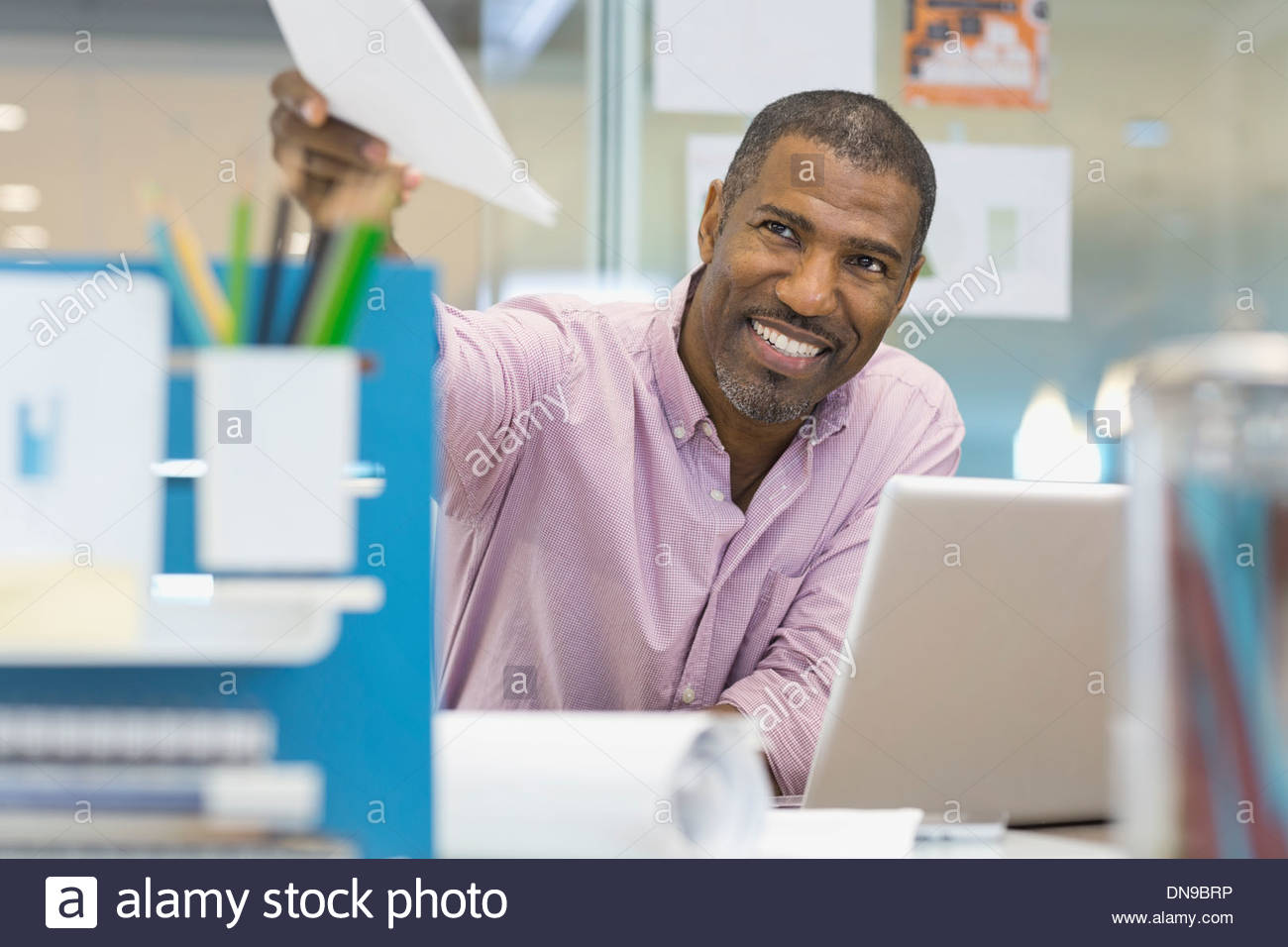 Businessman passing document in office - Stock Image