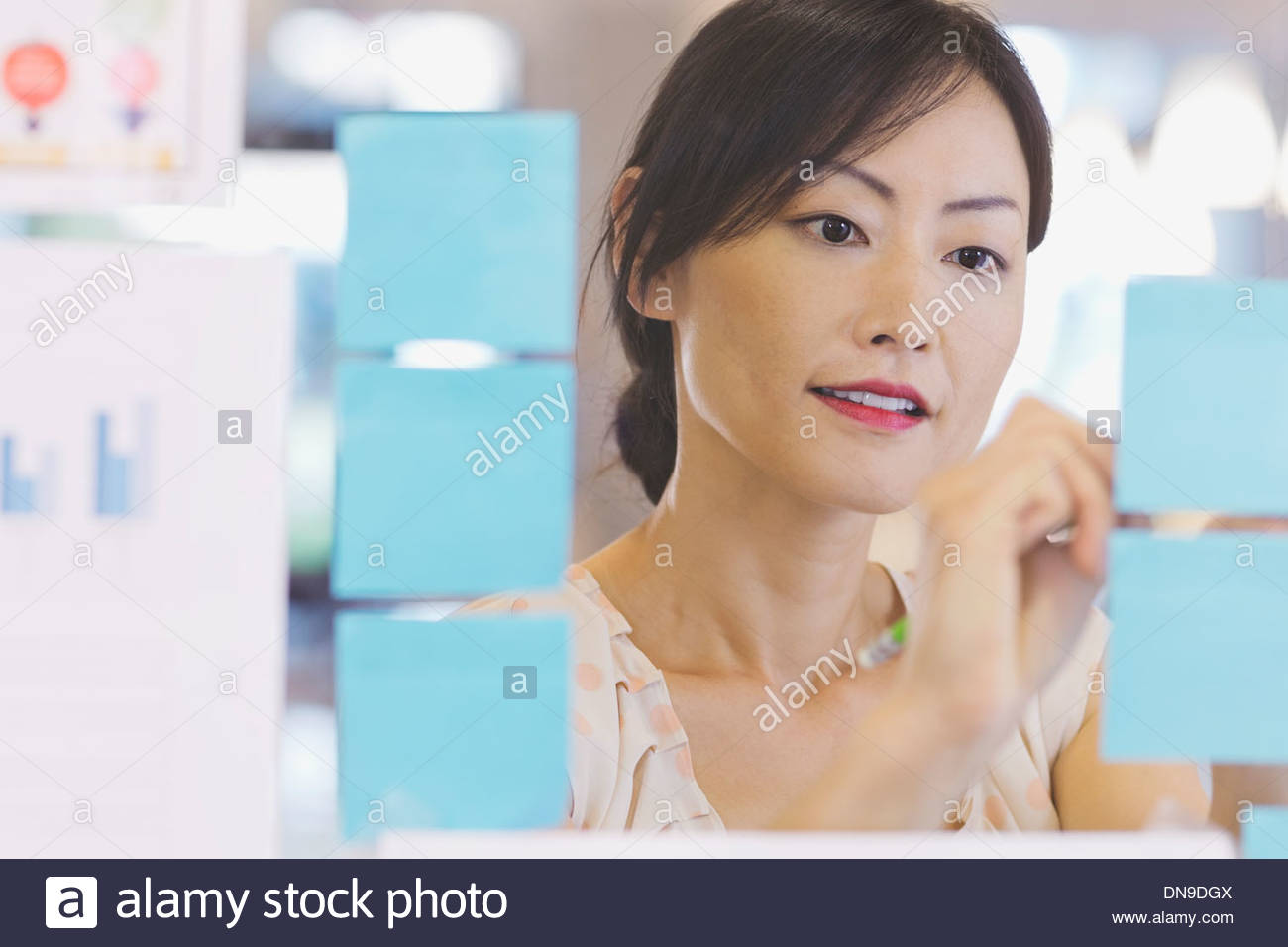 Businesswoman writing on adhesive notes in office - Stock Image