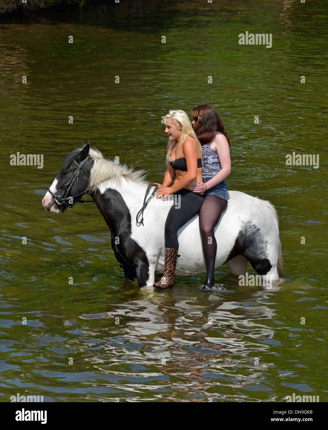 Gypsy traveller girls riding horse in River Eden. Appleby Horse Fair, June 2013. Appleby-in-Westmorland, Cumbria, England. - Stock Image