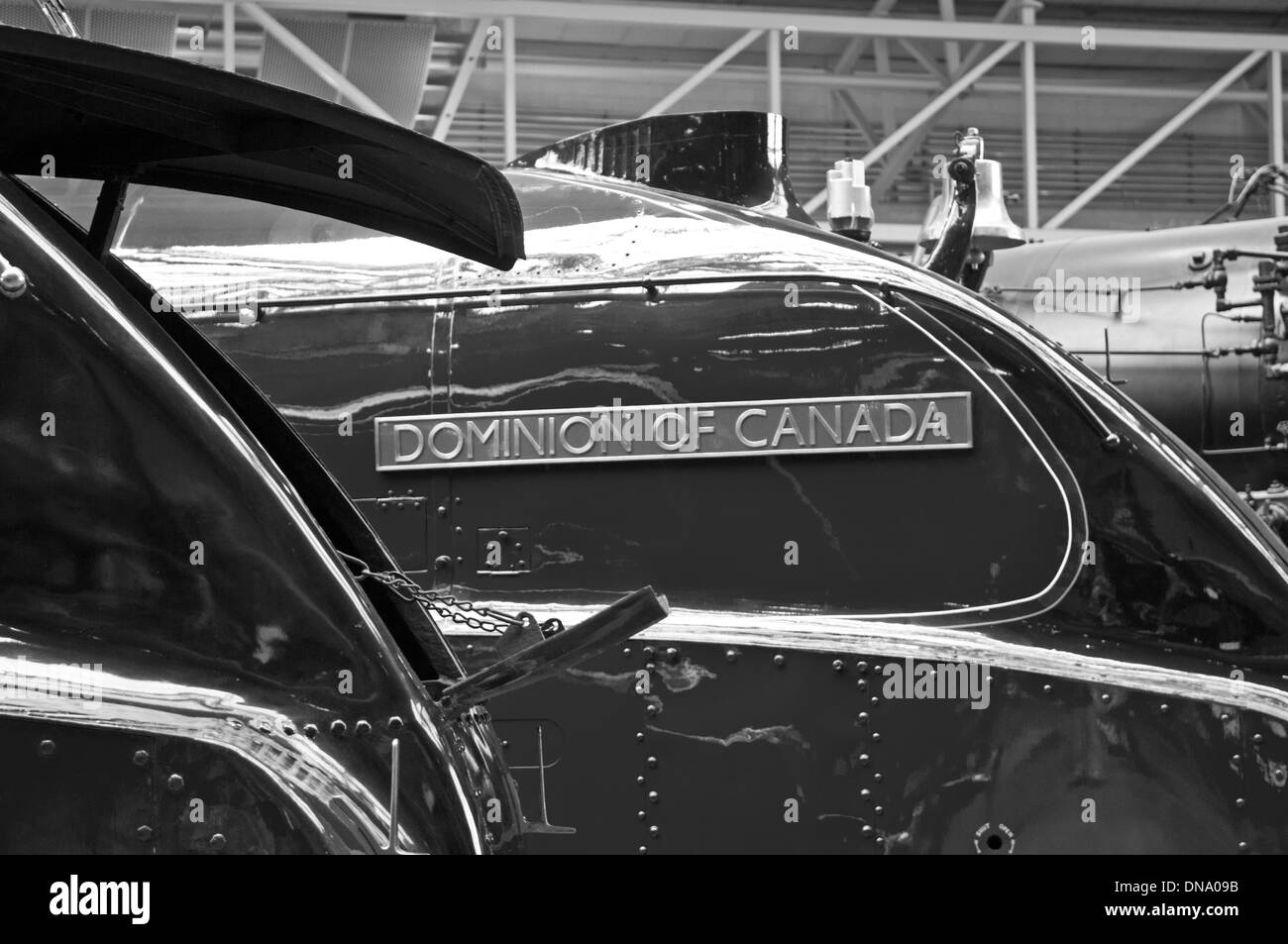 A4 Pacific Dominion of Canada name plate bracketed by the open streamline casing of Mallard in the National Railway Museum York. - Stock Image
