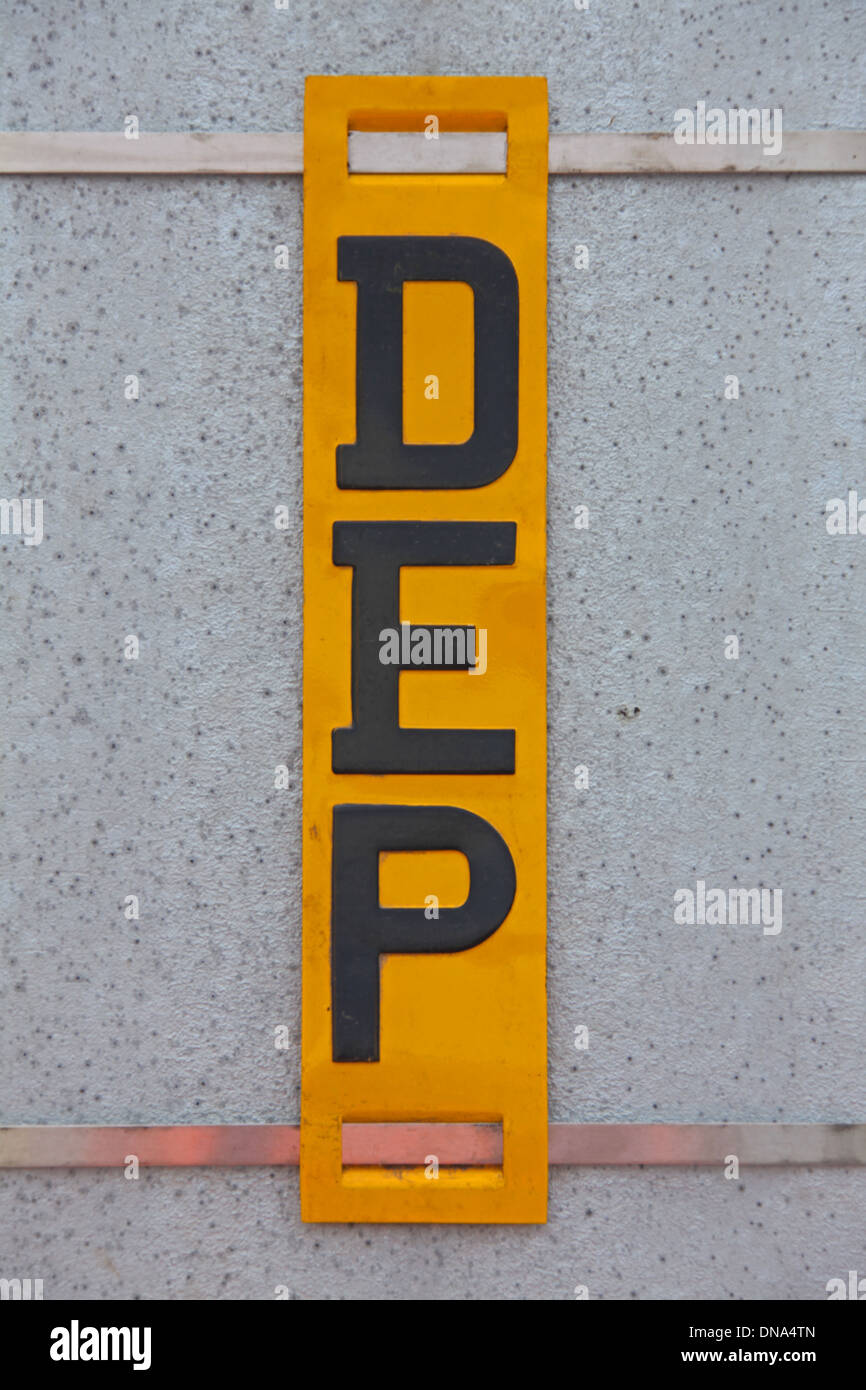 A metal yellow painted sign  with black letters  D E P vertically written attached to a steel beam with steel straps. - Stock Image