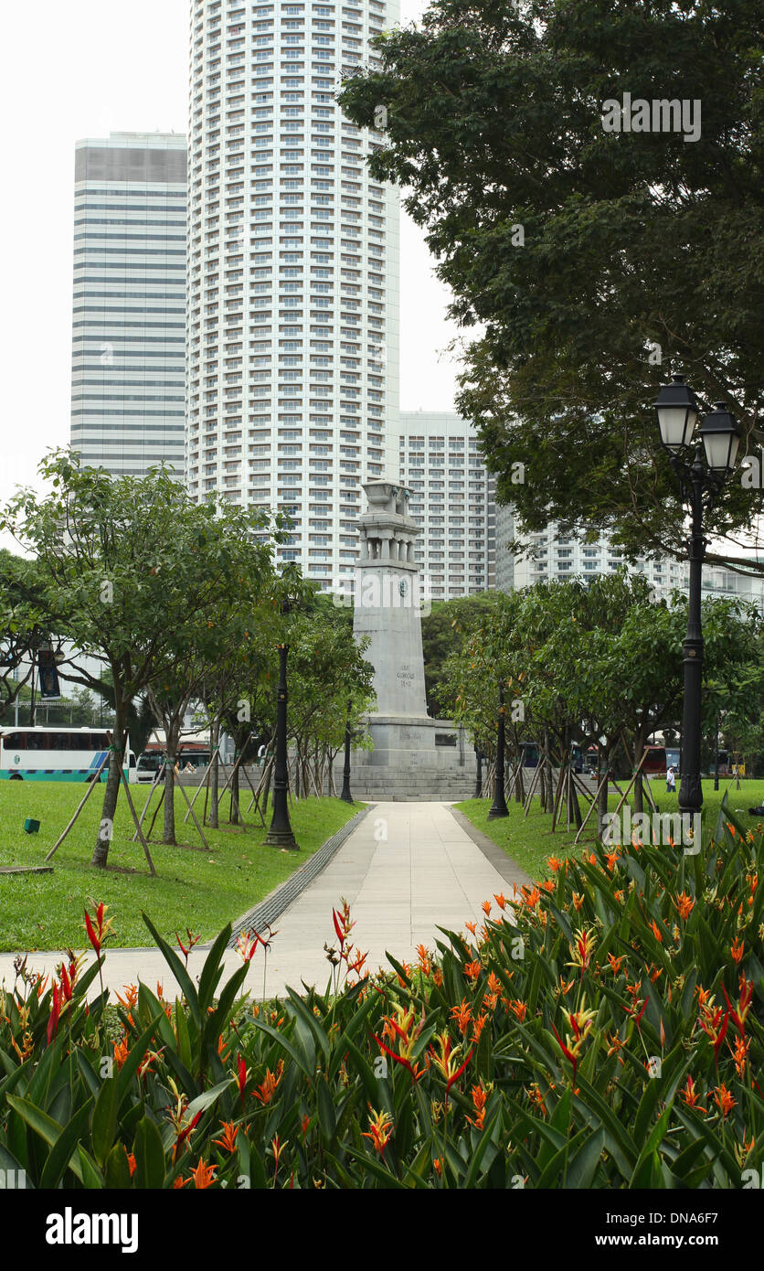The Cenotaph. Monument in Esplanade Park. Singapore. Background buildings are the Raffles City Shopping Centre. - Stock Image