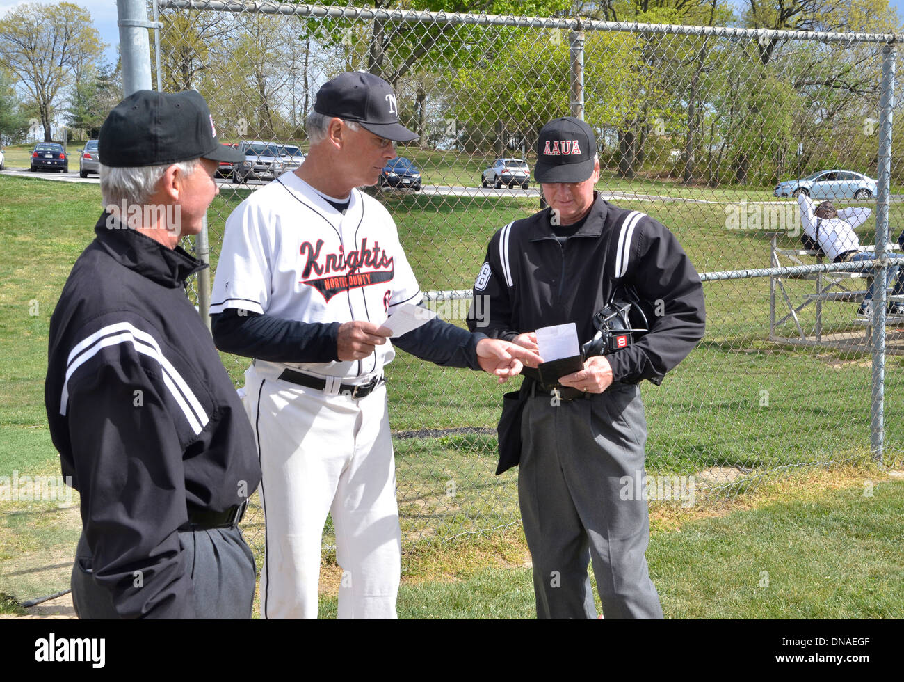coach gives lineups to umpires in a baseball game - Stock Image