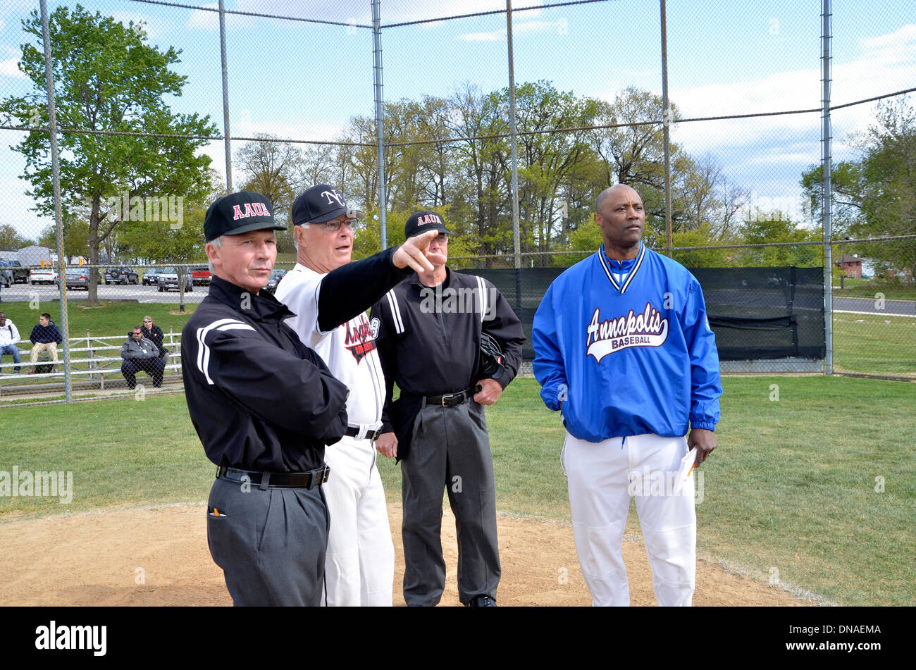 coach explain the field layout to the umpires in a baseball game - Stock Image