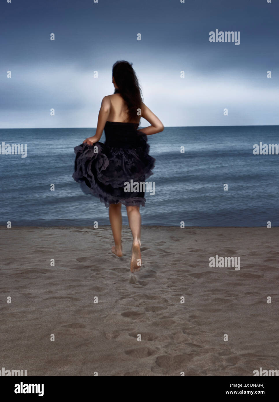 Young woman in black dress running towards the shore, rear view Stock Photo
