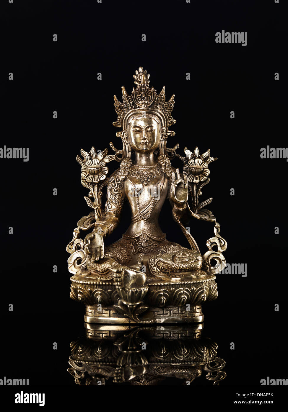 Green Tara statue Buddhist goddess of compassion. Isolated on black background. - Stock Image