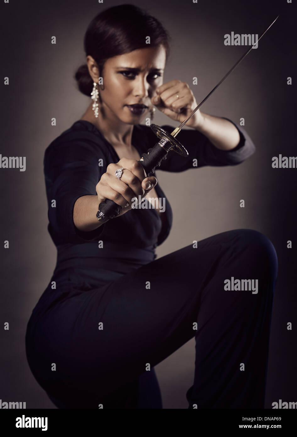 Young black woman with fierce expression in a defending pose with a Japanese Tanto knife, short sword in her hand - Stock Image