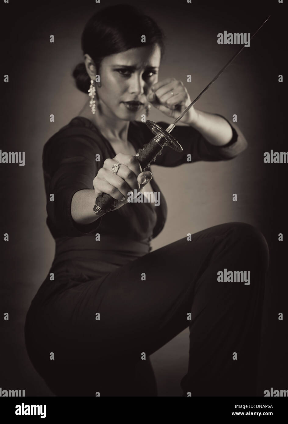 Young black woman with fierce expression in a defending pose with a Japanese Tanto knife, short sword in her hand Black white - Stock Image