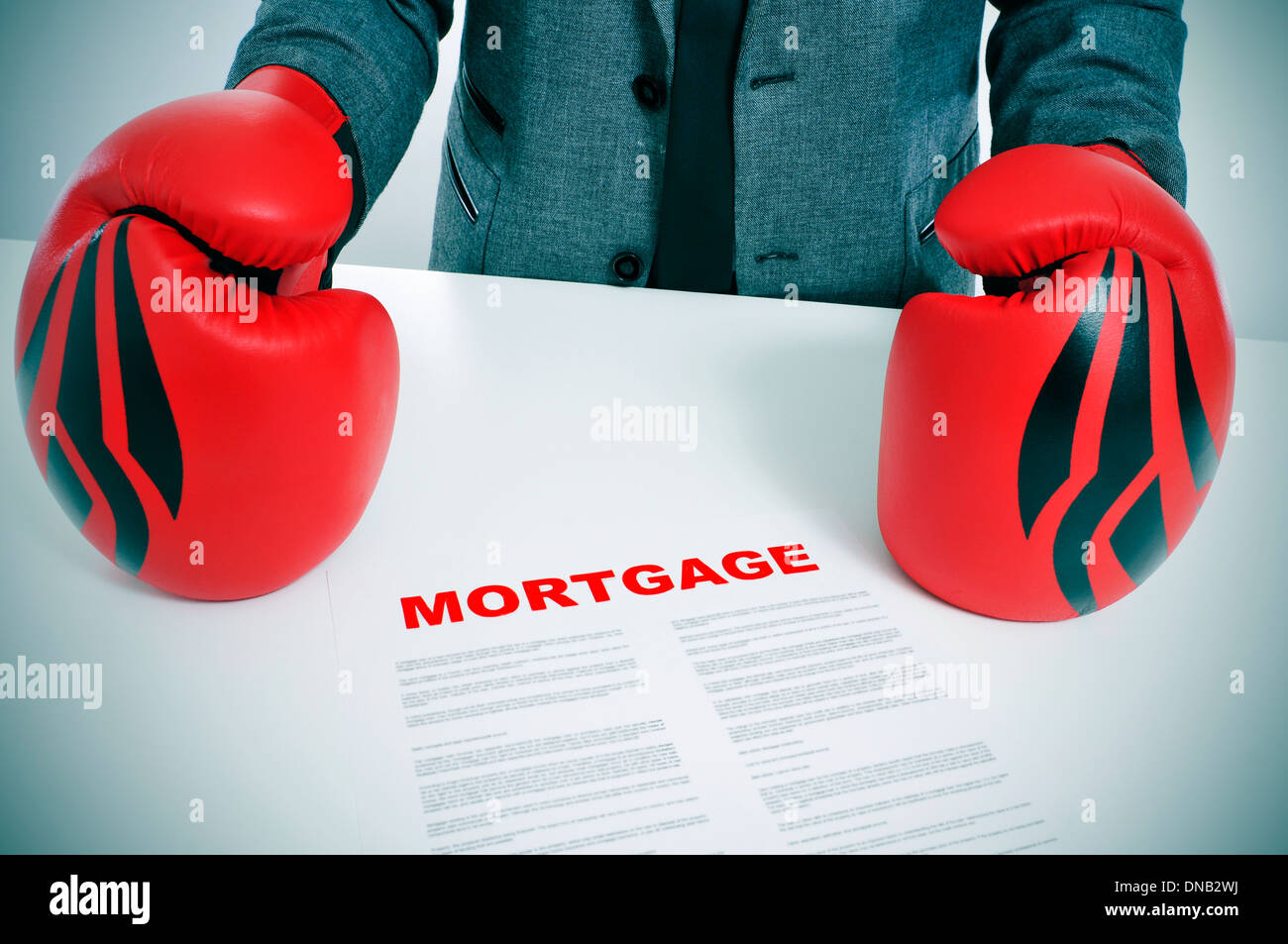 man wearing a suit and boxing gloves with a mortgage contract on his desk - Stock Image
