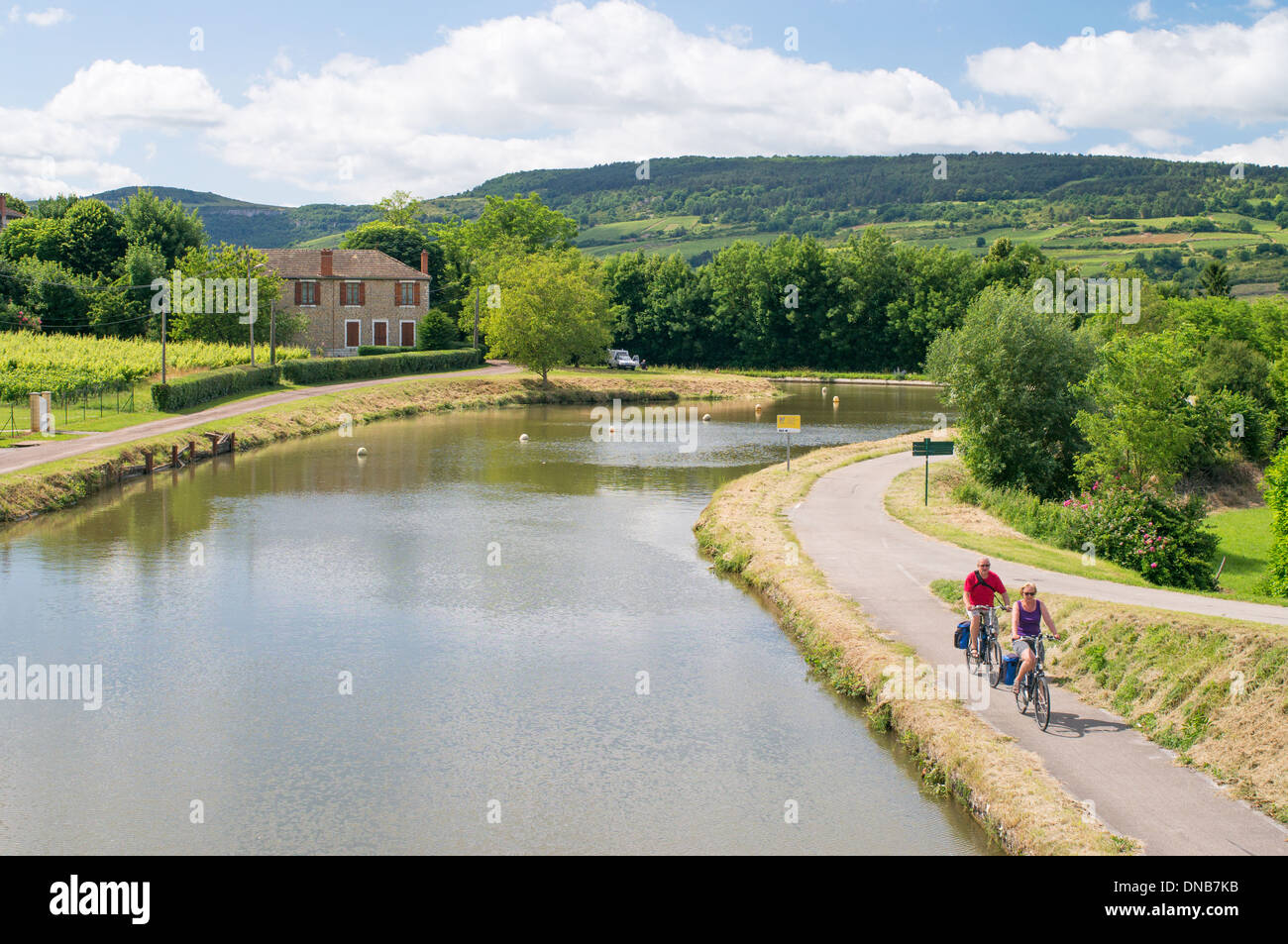 Couple cycling along the towpath of the Canal du Centre at Remigny in Burgundy France Europe - Stock Image