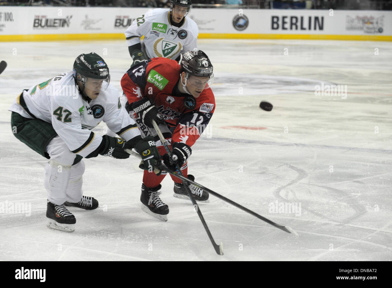 Berlin, Germany. 20th Dec, 2013. Joakim Hilding (L-R) of Farjestad BK vies for the ball with Laurin Braun of Eisbaren Berlin during the ice hockey European Trophy final Group A match Eisbaeren Berlin vs Farjestad BK at the O2 World in Berlin, Germany, 20 December 2013. Photo: Oliver Mehlis/dpa/Alamy Live News - Stock Image