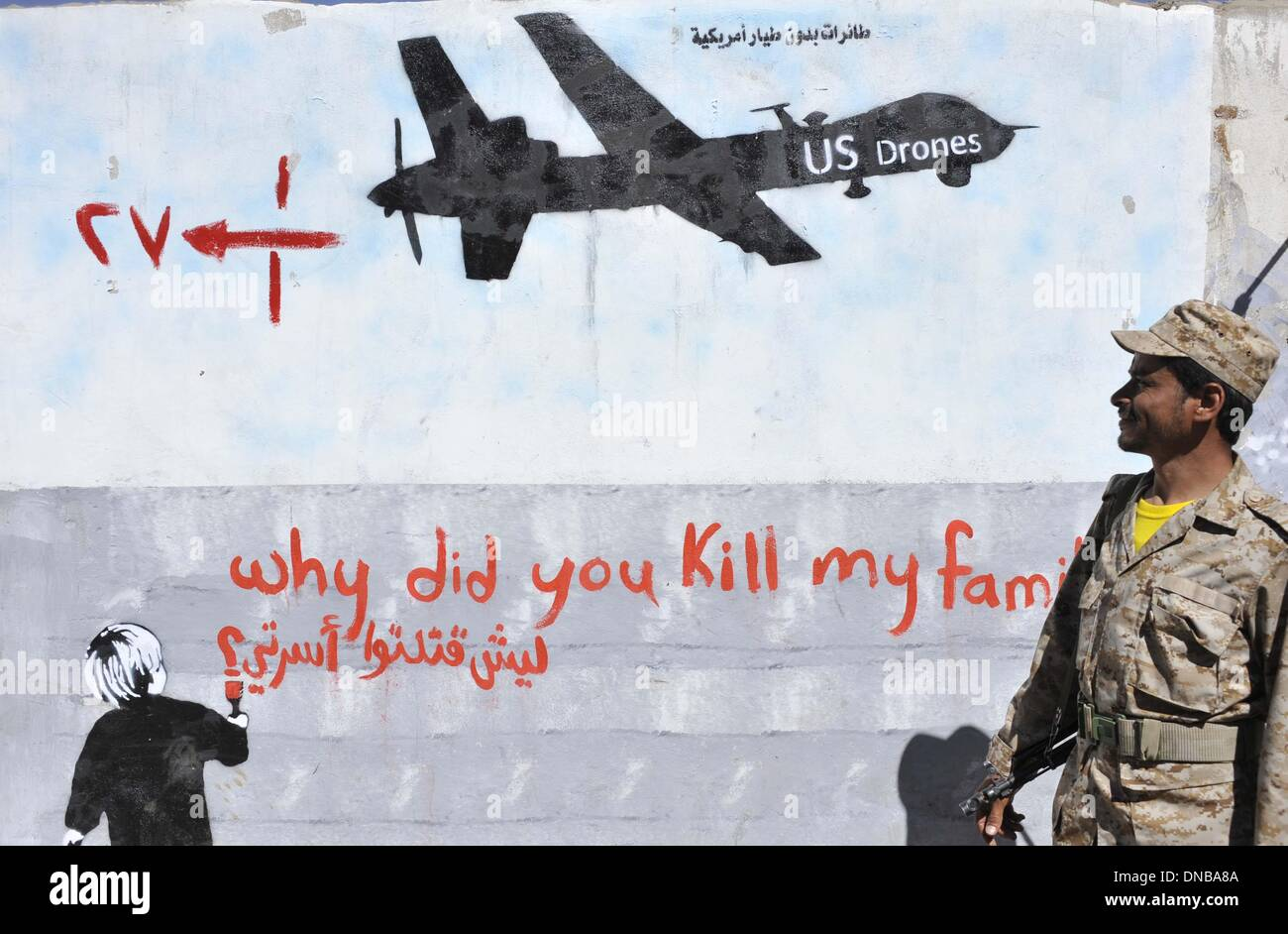 Sanaa, Yemen. 21st Dec 2013. A Yemeni soldier looks at the graffiti of U.S. drone strike painted on a wall as a protest against the drone strikes, in Sanaa, Yemen, on Dec. 21, 2013. The Yemeni parliament on Sunday approved a ban on U.S. drones in the country after dozens of civilians were killed by the unmanned aircraft, the official Saba news agency reported. The decision was made after the U.S. drone mistakenly hit a wedding convey on Thursday in Yemen's southeastern province of al- Bayda, killing up to 17 Yemeni civilians and wounding about 21 others. Credit:  Xinhua/Alamy Live News Stock Photo