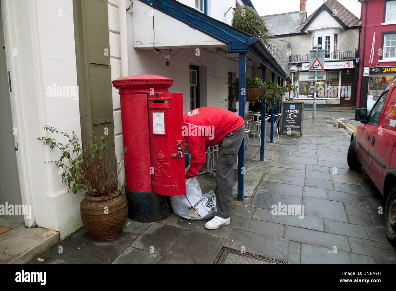 Post office worker filling his mail sack from a red pillar post box in Llandovery Carmarthenshire Wales UK  KATHY DEWITT - Stock Image