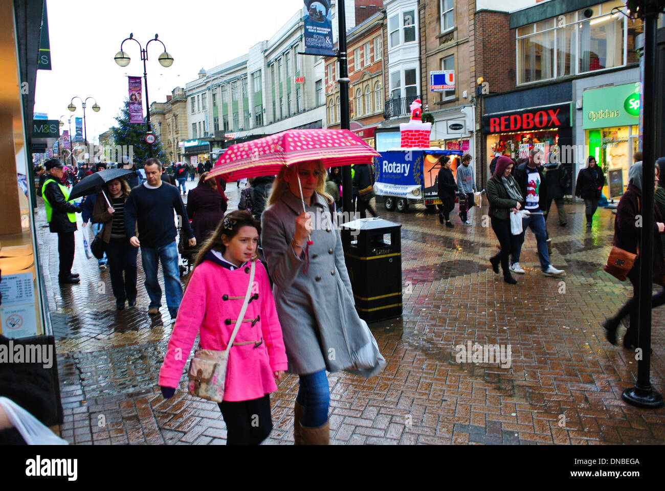 Northampton, UK. 21st Dec 2013. Christmas shoppers get wet buying presents on the busiest retail day of the year. Credit:  Bigred/Alamy Live News - Stock Image