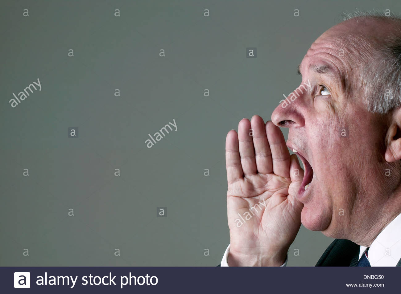 Senior businessman shouting with his hand to his mouth. - Stock Image