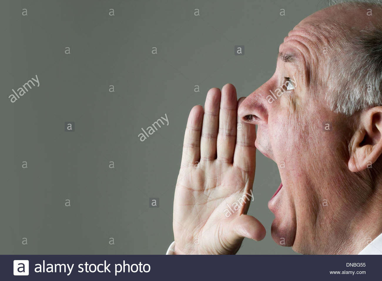 Senior man shouting with his hand to his mouth. - Stock Image
