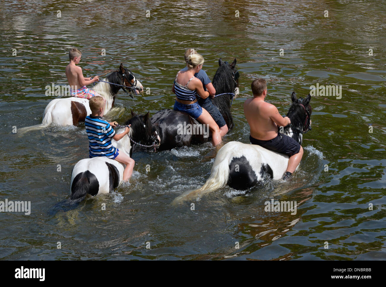 Gypsy travellers riding horses in River Eden. Appleby Horse Fair, Appleby-in-Westmorland, Cumbria, England, United Kingdom. - Stock Image