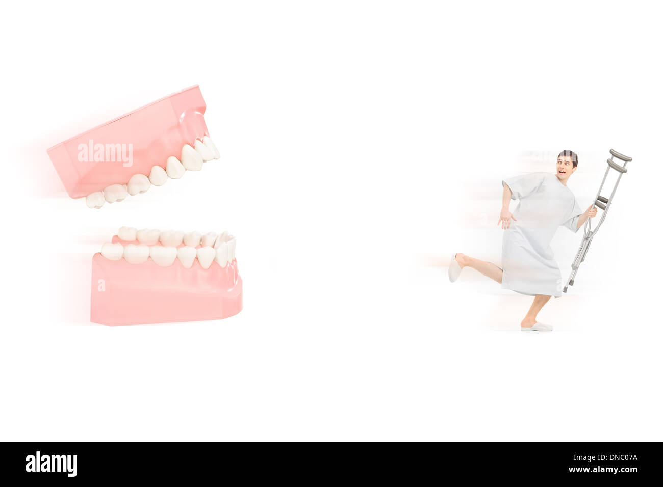 Afraid male patient in hospital gown with crutch running away from open dentures Stock Photo
